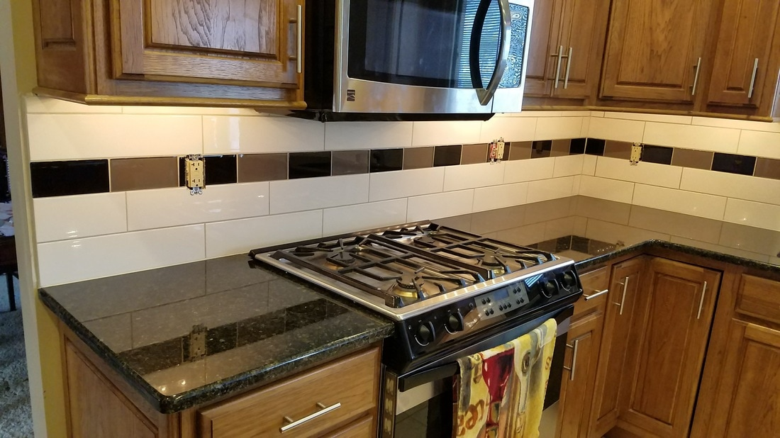 subway tile with black and brown glass design stripe oven close up